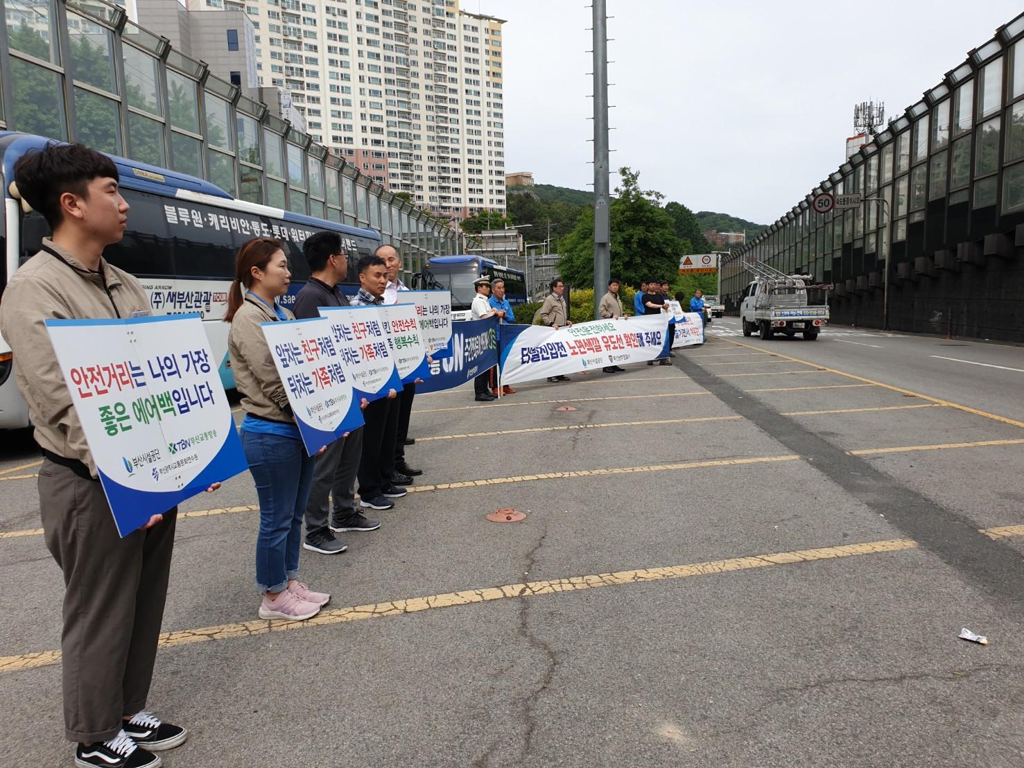 황련터널 전포방면 입구에서 교통문화정착 위한 캠페인 피켓과 현수막을 들고 사람들이 서 있다.(측면사진)